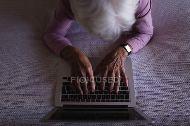Overhead view of an active senior woman lying on her bed and using a laptop in bedroom at home — Stock Photo