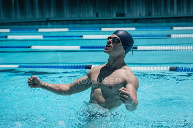 Боковой вид молодого кавказского пловца с вытянутыми руками, чтобы отпраздновать победу в открытом бассейне в солнечный день — стоковое фото