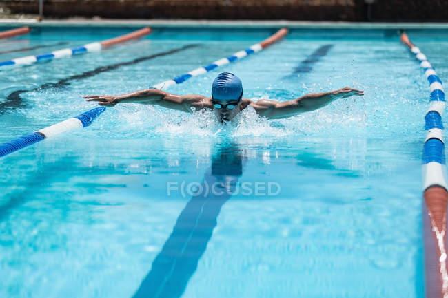 Вид спереди на молодого кавказского пловца в середине инсульта бабочки в открытом бассейне под солнцем — стоковое фото