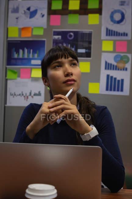 Vorderansicht einer nachdenklichen Geschäftsfrau, die im Büro träumt — Stockfoto
