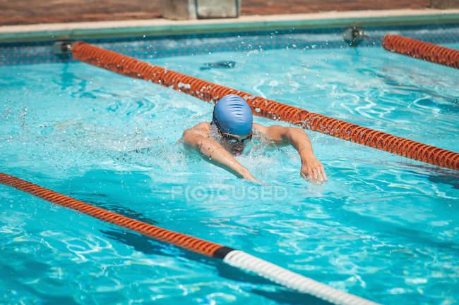 Seitenansicht des jungen kaukasischen männliche Schwimmer schwimmen Schmetterlingsstil im Außenpool in der Sonne — Stockfoto