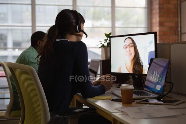 Rückansicht einer Geschäftsfrau, die am Schreibtisch ihren Geschäftspartner im Büro per Video anruft — Stockfoto