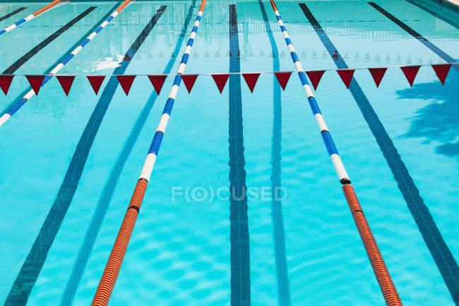 Высокий угол зрения бирюзовый пустой открытый бассейн с флагом гирлянды в Солнечный день — стоковое фото
