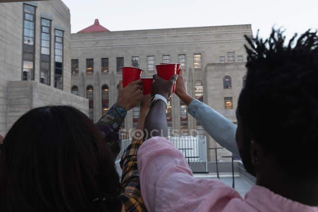 Vue arrière de divers amis griller avec boisson froide dans le balcon à la maison — Photo de stock