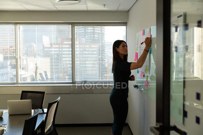 Вид сбоку молодых довольно женского исполнительной надписи на красочные записки в современном офисе — стоковое фото