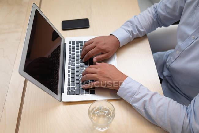 Ansicht eines Geschäftsmannes, der an seinem Laptop arbeitet, während er am Schreibtisch im Büro sitzt — Stockfoto
