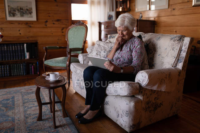 Front view of an active senior woman using a digital tablet while sitting on the sofa at home for the teatime — Stock Photo