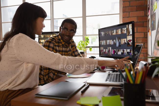 Фронтальный вид различных бизнесменов, обсуждающих за ноутбуком в офисе. Они смотрят друг на друга. — стоковое фото