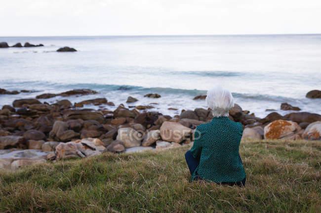 Вид сзади вдумчивый активные старший женщина, сидящая на траве на пляже и глядя на море — стоковое фото