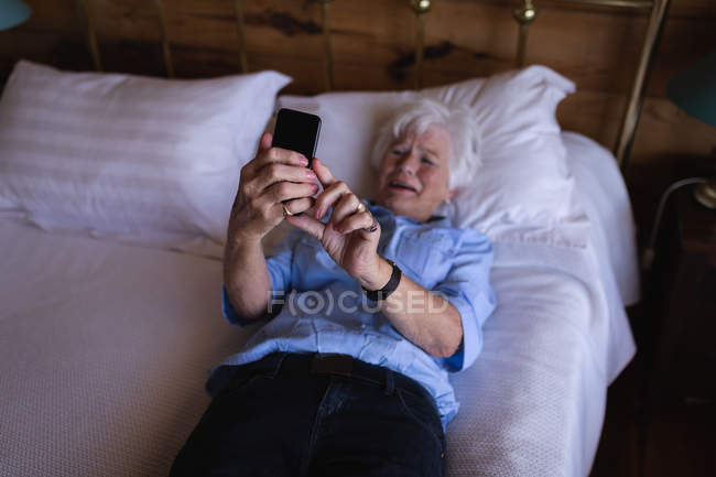 High angle view of a sad active senior woman using her mobile phone while lying on bed in bedroom at home — Stock Photo