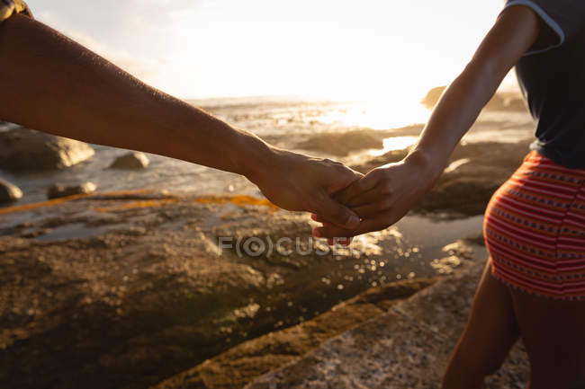 Close up of African-american couple holding hands and standing on rock near sea side — Stock Photo
