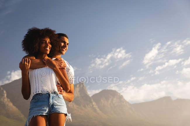 Low angle view of African-american couple standing together in romantic mood near sea side — Stock Photo