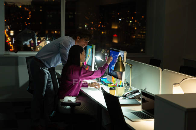 Side view of young multi-ethnic office executives working on desktop pc at desk in a modern office — Stock Photo