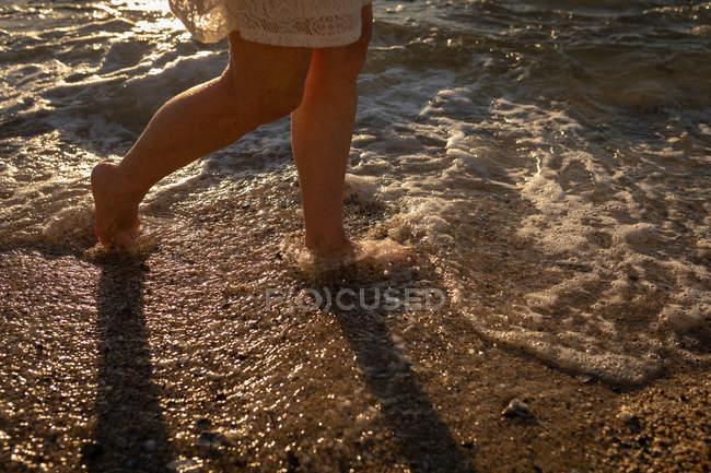 Нижняя часть активной пожилой женщины, идущей по берегу моря вечером с закатом, отражающимся на воде — стоковое фото
