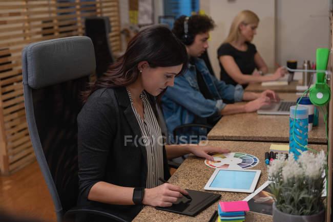 Vista lateral de la mujer de negocios caucásica usando tableta gráfica mientras mira la muestra de color en la oficina mientras sus colegas trabajan detrás de ella - foto de stock