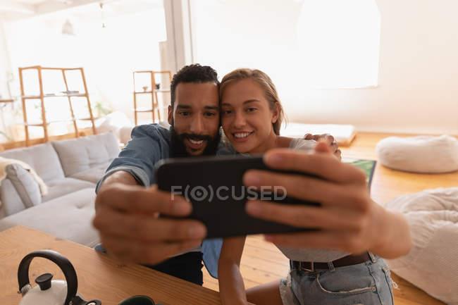 Vue de face du couple ethnique prenant selfie dans le salon à la maison — Photo de stock