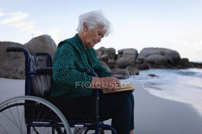Side view of a disabled active senior woman reading a book on a wheelchair next to the water on the beach — Stock Photo