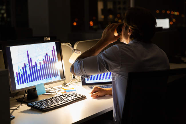Rear view of young male executive drinking coffee while working at desk in a modern office. He is working late — Stock Photo