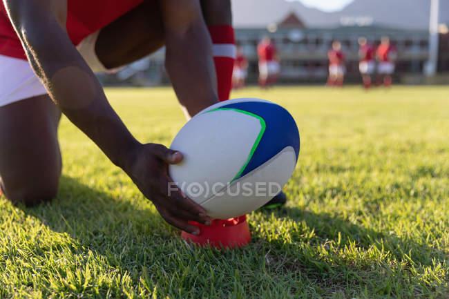 Закри молоді чоловіки регбіст, поставивши м'яч регбі на ногами tee на стадіоні — стокове фото