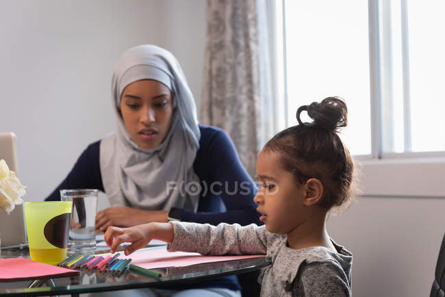 Vista frontal de la mujer corrió mezclada con hijab e hija hablando con los demás en casa sentado en la silla alrededor de una mesa - foto de stock