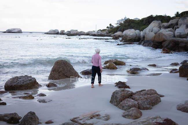 Вид сзади активные старший женщину, ходить на берегу пляжа — стоковое фото
