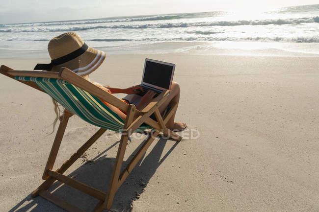 Vue arrière de la jeune femme se détendre sur une chaise longue à la plage par une journée ensoleillée. Elle utilise son ordinateur portable — Photo de stock