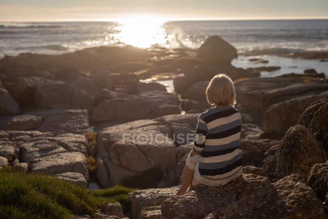 Visão traseira de uma mulher idosa ativa relaxando na rocha e olhando para o pôr do sol na praia — Fotografia de Stock