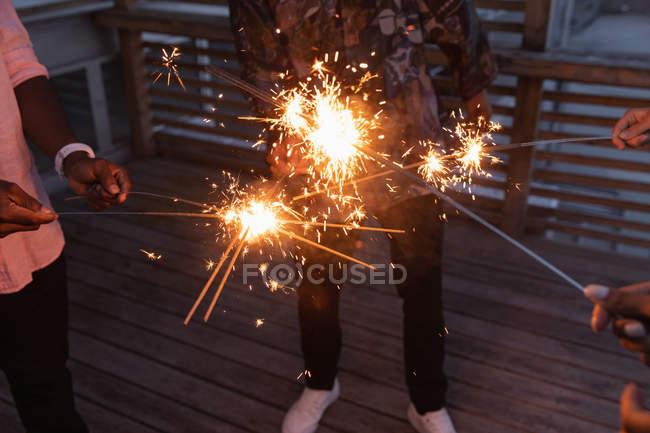 Groupe multi ethnique amis appréciant dehors avec feux de Bengale en balcon à la maison — Photo de stock