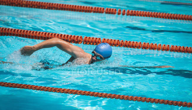 Seitenansicht des jungen kaukasischen männliche Schwimmer Schwimmen Freistil im Schwimmbad an sonnigen Tag — Stockfoto