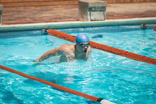 Vorderansicht des jungen kaukasischen männliche Schwimmer schwimmen Schmetterlingsstil im Swimmingpool im Freien an sonnigen Tag — Stockfoto