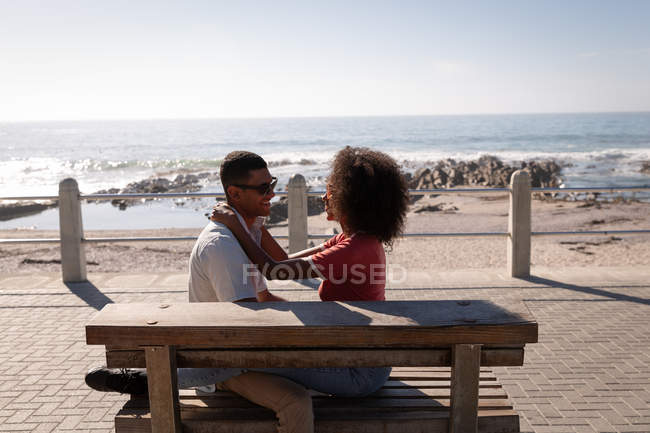 Side view of African-american couple in romantic mood sitting on wooden plank near sea side. They are sitting face to face while smiling — Stock Photo