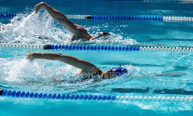 Вид сбоку на юношей и девушек, плавающих в бассейне в солнечный день — стоковое фото