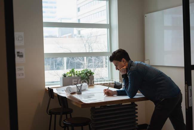 Vue latérale de l'homme d'affaires permanent et travaillant sur le plan à la conférence de l'office — Photo de stock