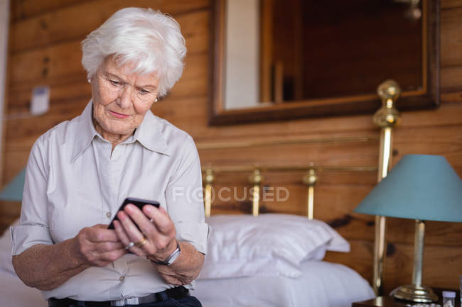 Front view of an active senior woman sitting on the bed and using her mobile phone in bedroom at home — Stock Photo