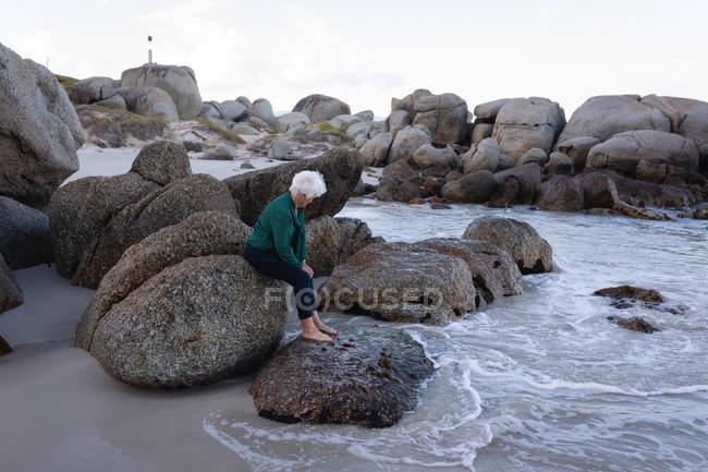 Вид сбоку активные старший женщина, сидящая на скалах на пляже — стоковое фото