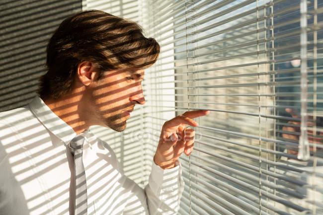 Вид сбоку красивый молодой мужской Исполнитель, глядя через окно жалюзи в современном офисе — стоковое фото