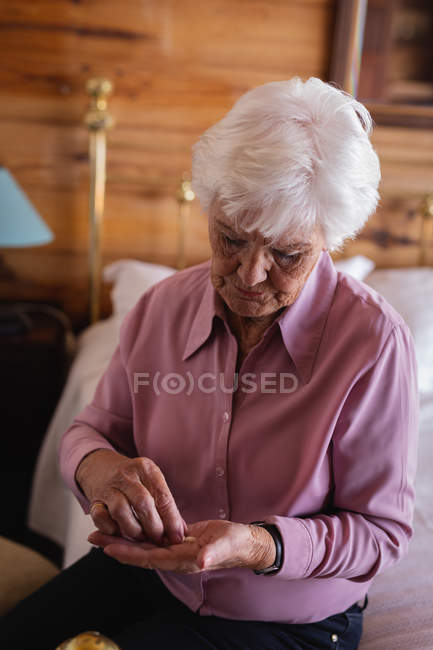 Front view of an active senior woman taking medicine in bedroom at home — Stock Photo