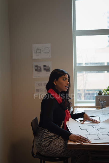 Side view of African-american businesswoman discussing over blueprint in conference room at office — Stock Photo