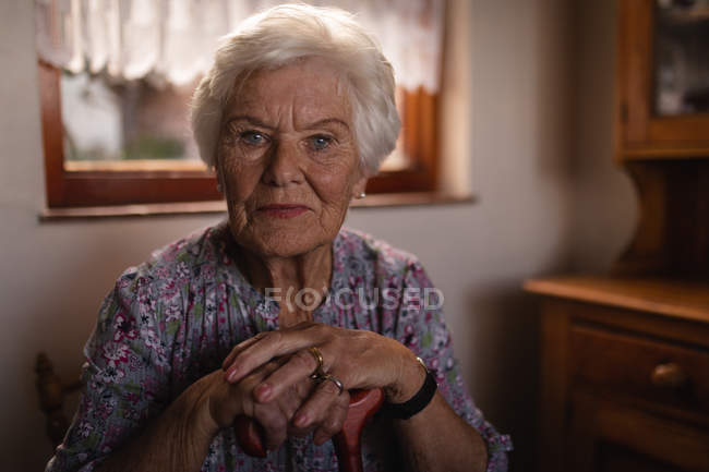 Portrait of an active senior woman sitting with her cane and looking at the camera in the kitchen at home — Stock Photo