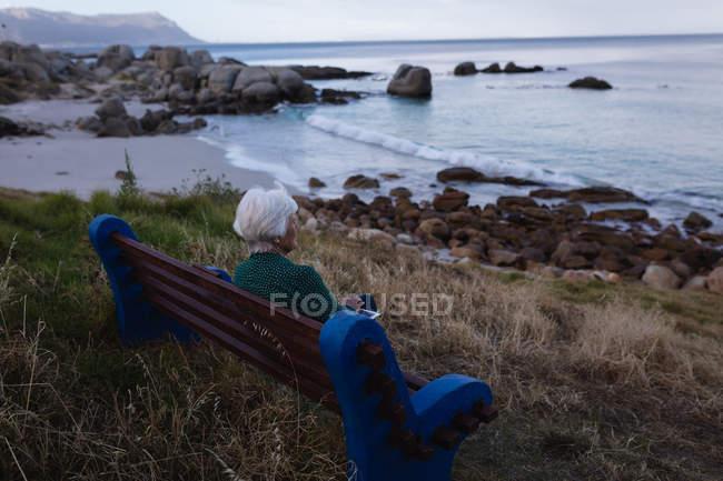 Вид сзади вдумчивый активные старший женщина, держащая цифрового планшета пока сидящ на деревянной скамье на море — стоковое фото