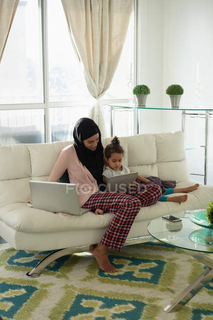 Front view of mixed race mother wearing hijab talking with daughter while showing her digital tablet in living room at home — Stock Photo