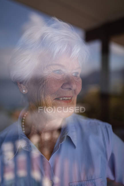 Close-up of a happy active senior woman looking trough the window at home — Stock Photo