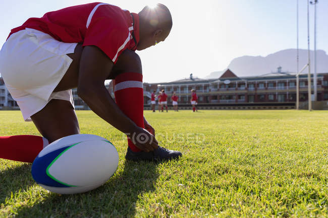 Вид збоку чоловічого афро-американських регбіст, прив'язавши його шнурків з регбі землю на сонці — стокове фото