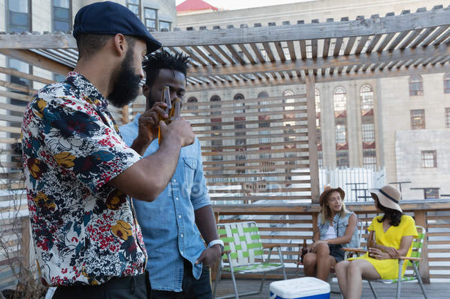 Side view of multi ethnic male friends toasting with beer bottles at home in balcony while female talking with each other — Stock Photo