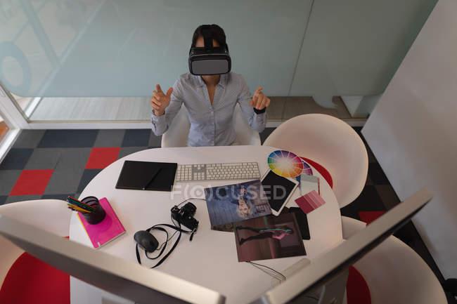 Visão de alto ângulo de uma empresária asiática usando um fone de ouvido de realidade virtual na mesa no escritório — Fotografia de Stock