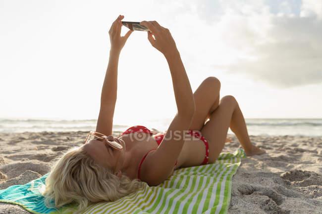 Vue arrière de la femme blonde prenant selfie à la plage par une journée ensoleillée. Elle porte des lunettes solaires — Photo de stock
