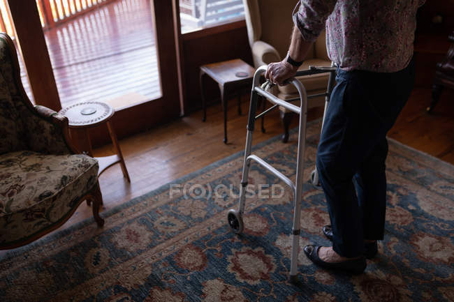 Low section of an active senior woman walking with a walker in the living room at home — Stock Photo