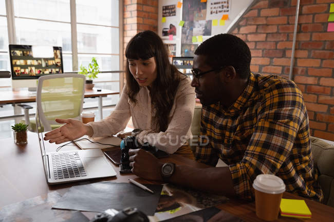 Front view of diverse business people discussing over laptop in office — Stock Photo