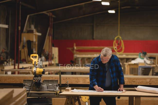 Vorderseite eines kaukasischen Tischlers, der in einer Werkstatt arbeitet — Stockfoto