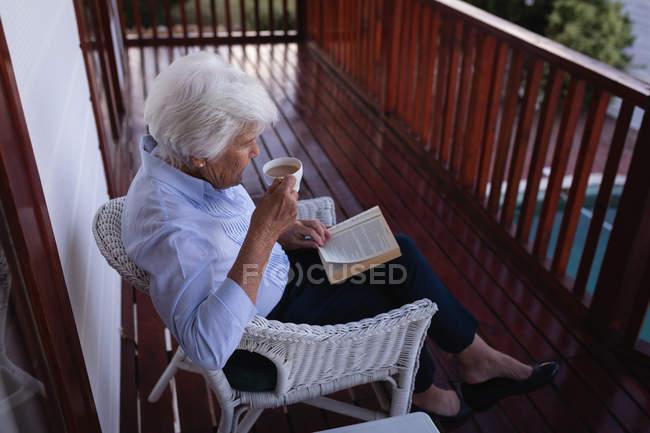 Blick auf eine aktive Seniorin, die Kaffee trinkt und auf dem Balkon sitzt, während sie zu Hause ein Buch liest — Stockfoto